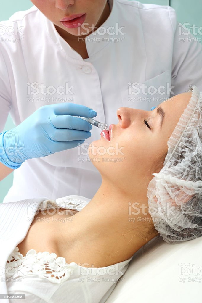 Beautiful woman gets an injection in her lips. royalty-free stock photo