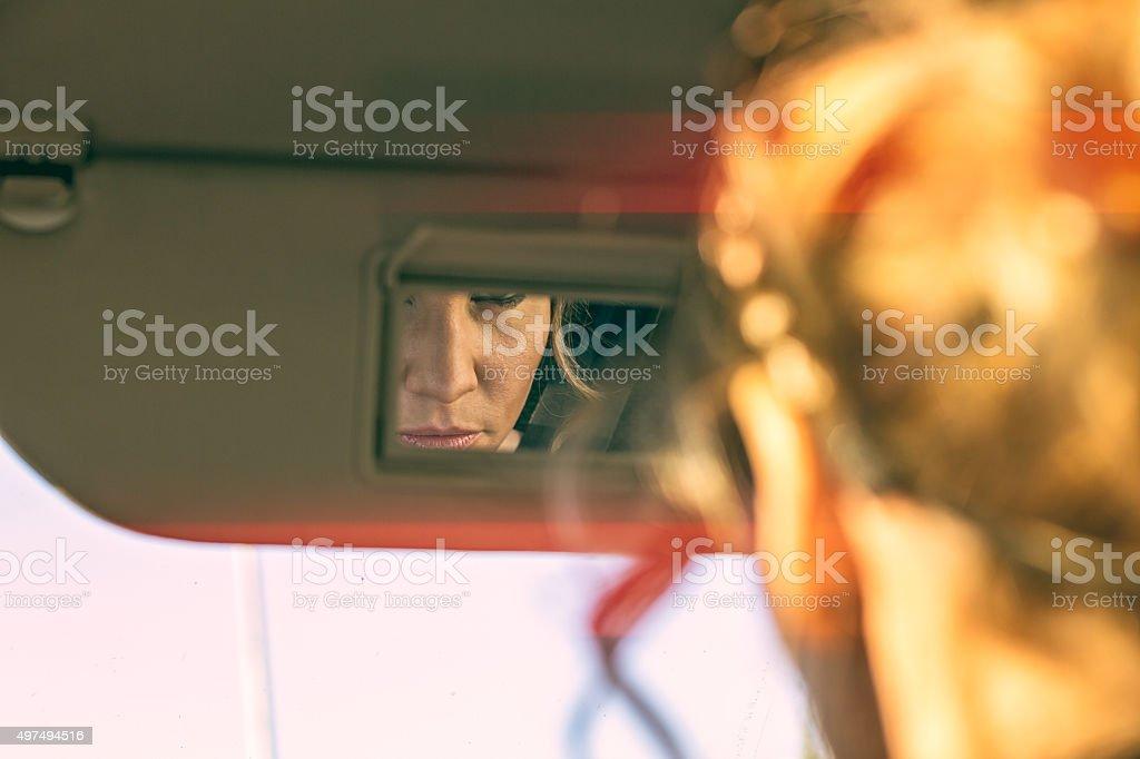 beautiful woman getting makeup in the car stock photo