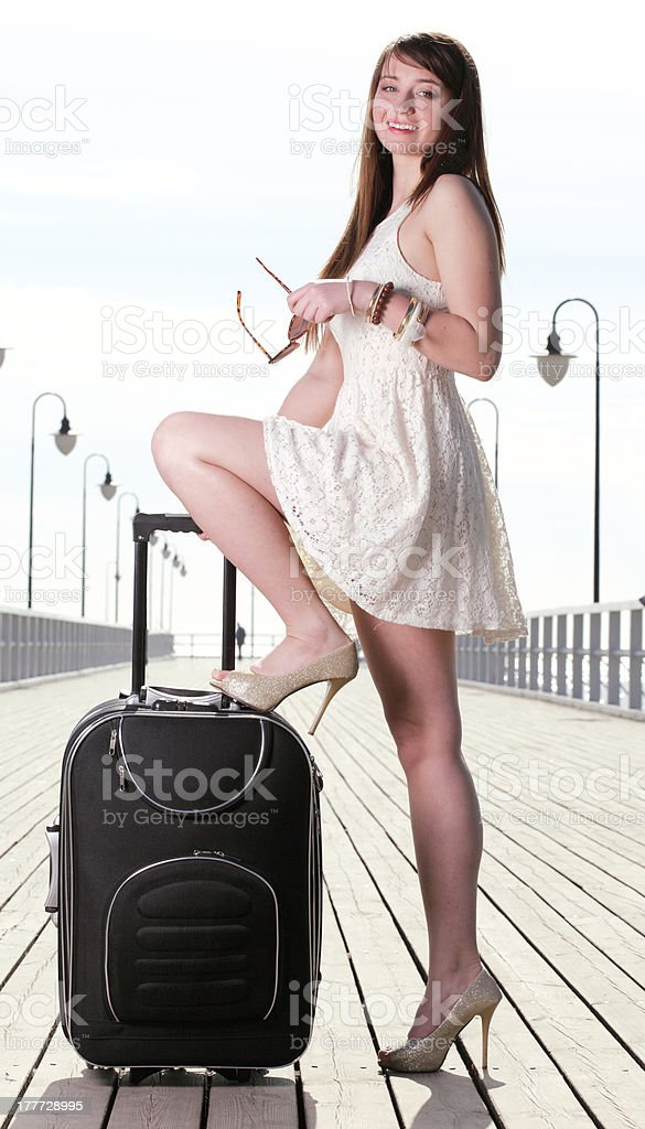 Beautiful woman girl sea mooring suitcase on a pier royalty-free stock photo