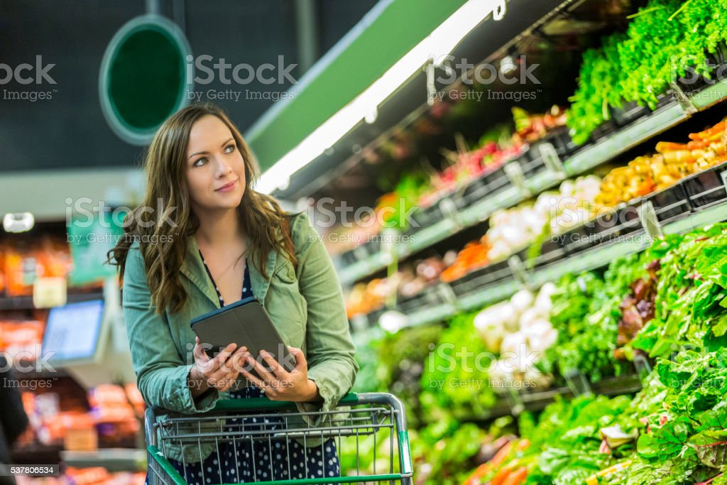 Beautiful woman grocery shopping with tablet stock photo