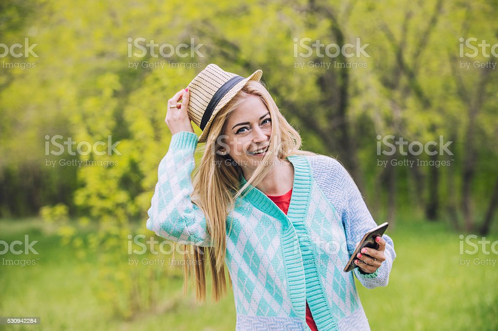 Beautiful woman happy and smiling with mobile phone in hand stock photo