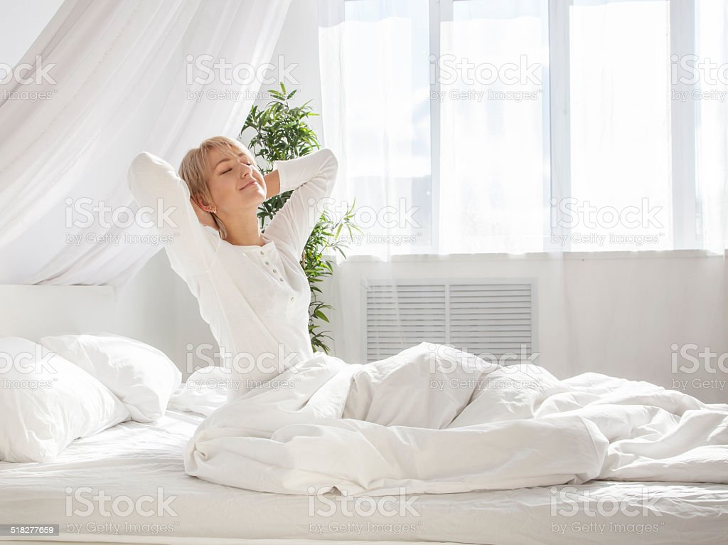 beautiful woman has woken up and is sitting stock photo