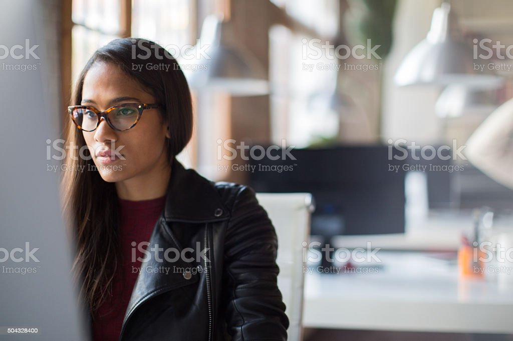 Beautiful woman highly concentrated working on computer. stock photo
