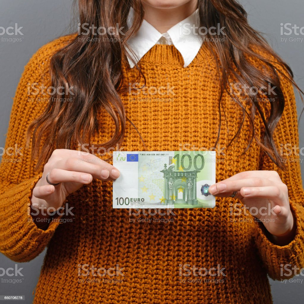 Beautiful woman holding 100 euros banknote against gray background stock photo