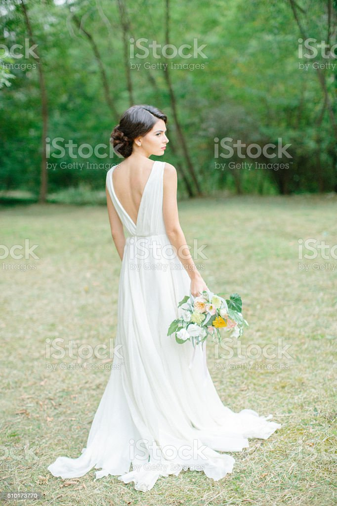 Beautiful woman holding a bouquet of flowers stock photo
