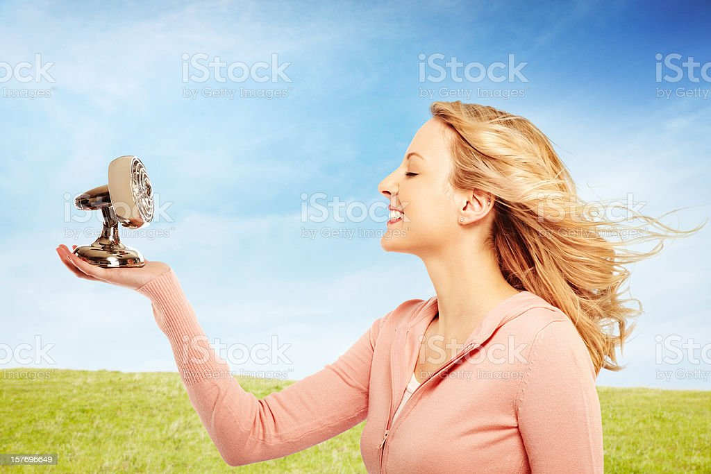 Beautiful woman holding a fan with hair blowing in wind royalty-free stock photo