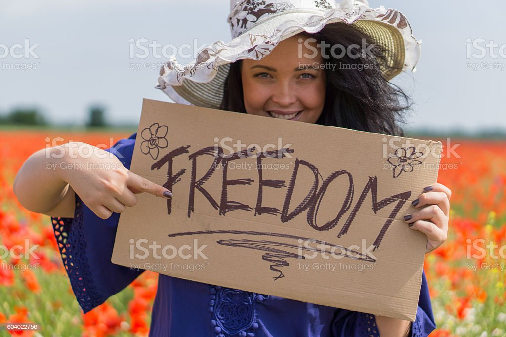 Beautiful woman holding a paper banner with text 'Freedom' stock photo