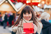 beautiful woman holding a present box on a christmas market