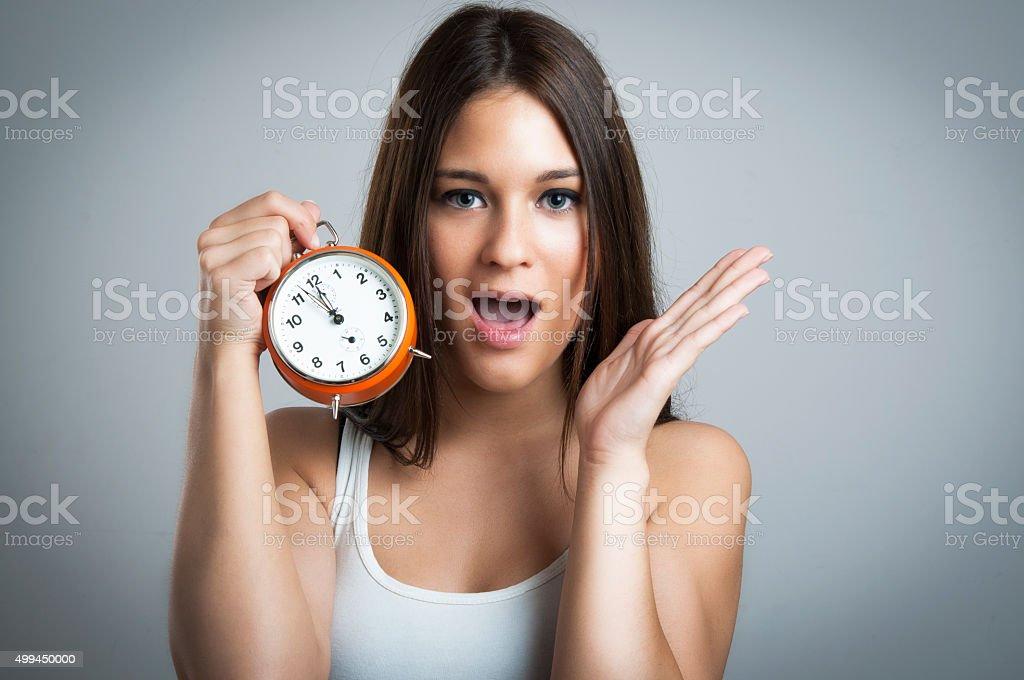 Beautiful  woman holding clock on gray background stock photo