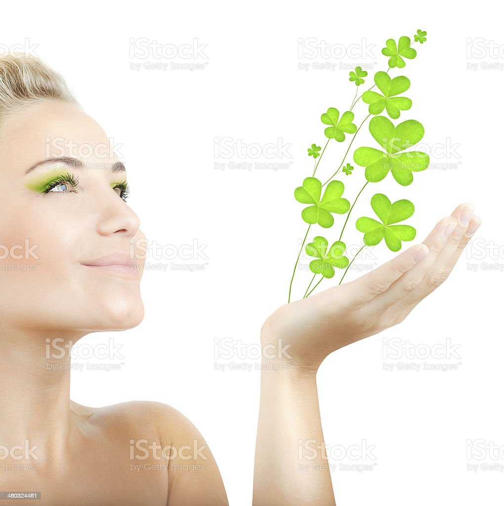 Beautiful woman holding clover leaves royalty-free stock photo