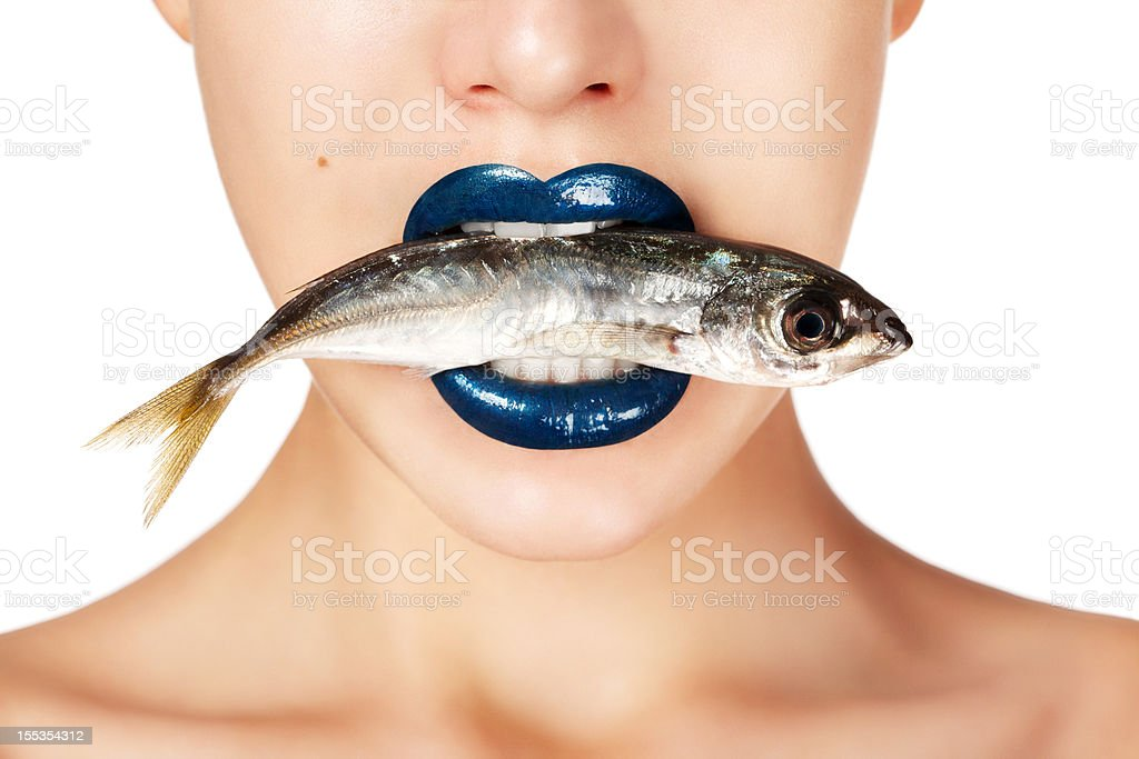 Beautiful woman holding fish in her mouth stock photo