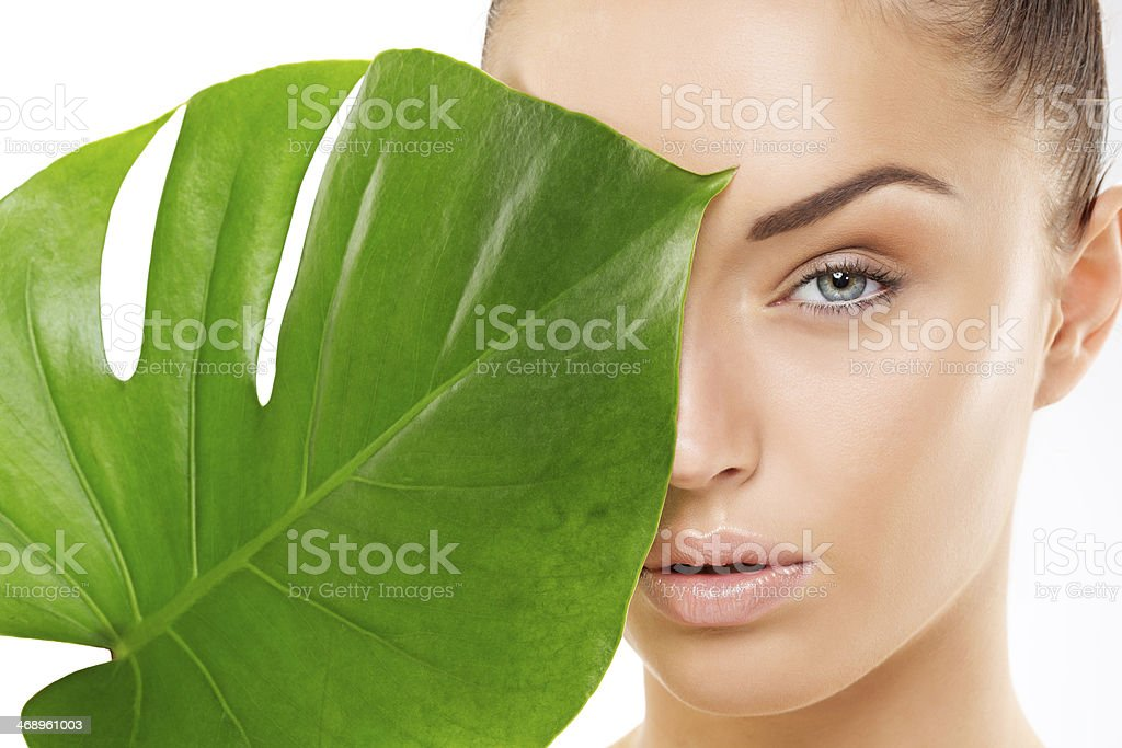 beautiful woman holding green leaf stock photo
