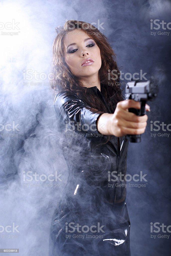 Beautiful woman holding gun. smoke background royalty-free stock photo