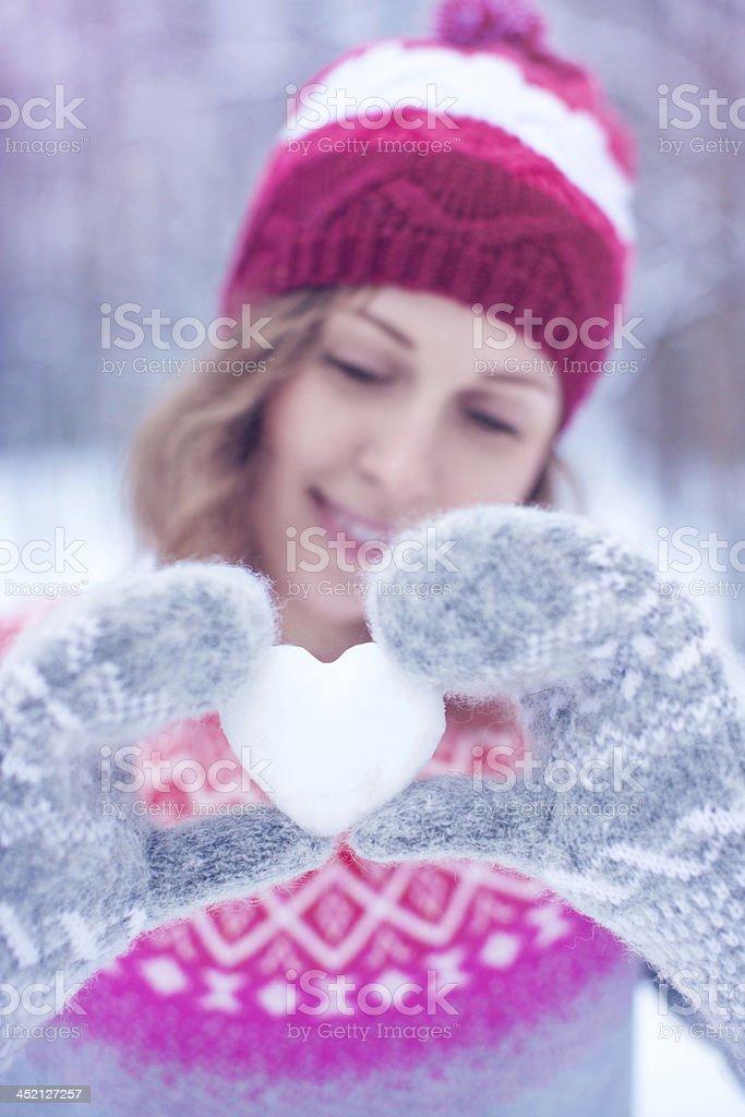 Beautiful woman holding heart-shaped snowball royalty-free stock photo