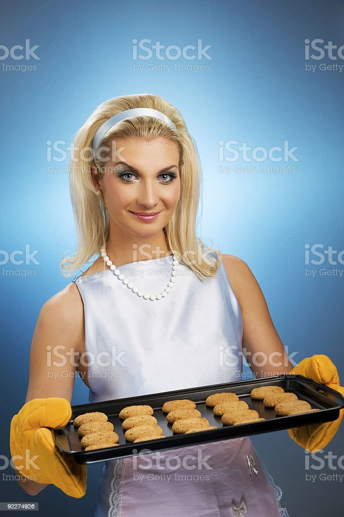 Beautiful woman holding hot roasting pan with oat cookies royalty-free stock photo