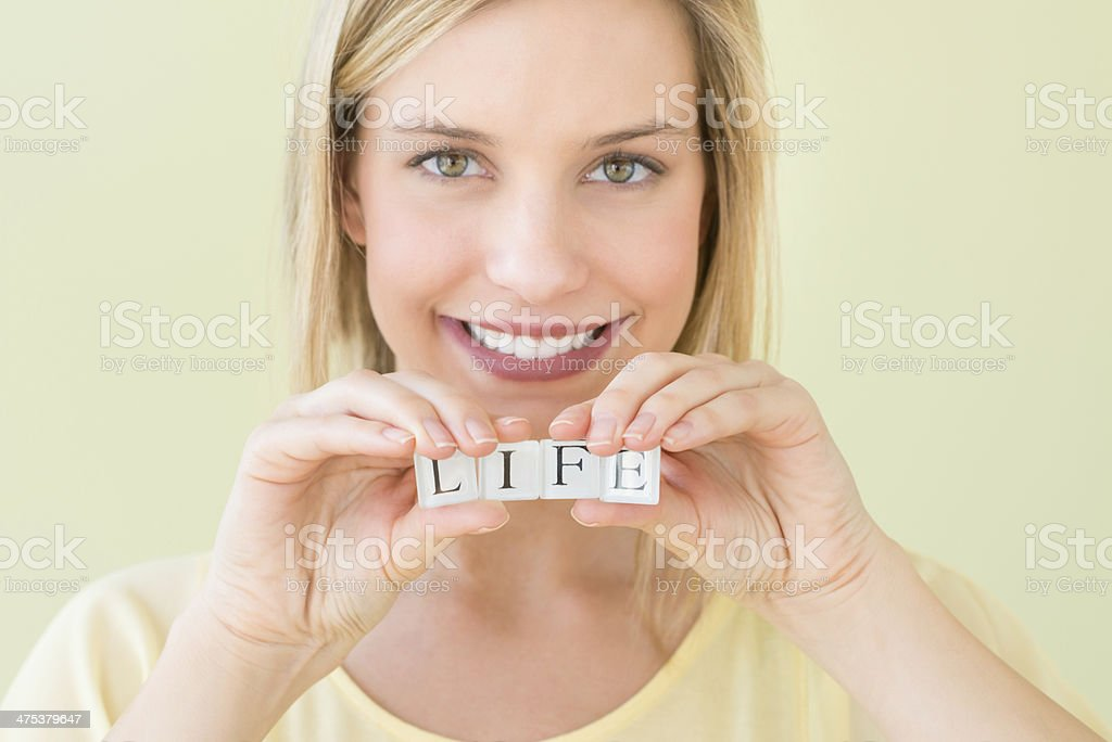 Beautiful Woman Holding Letter Blocks Reading Life royalty-free stock photo