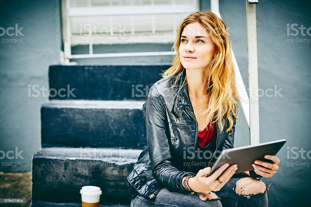 Beautiful woman holding tablet computer while sitting on steps stock photo
