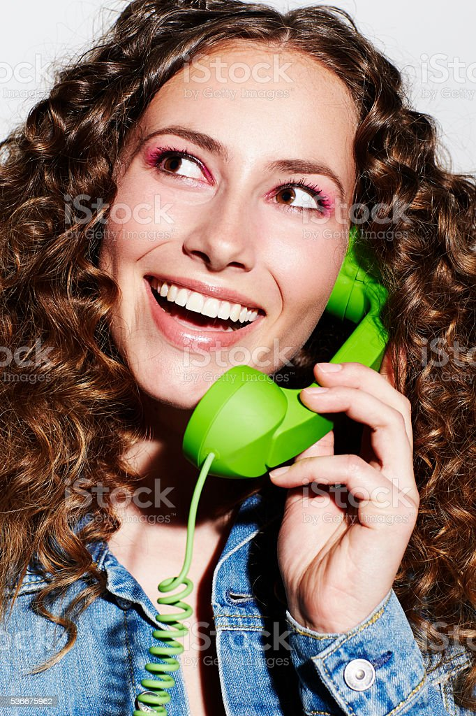 Beautiful woman holding telephone receiver, smiling stock photo