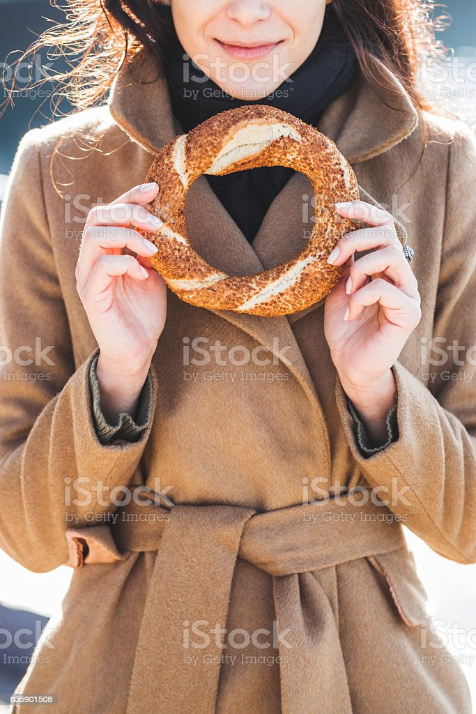 Beautiful woman holds a traditional Turkish simit in hands stock photo