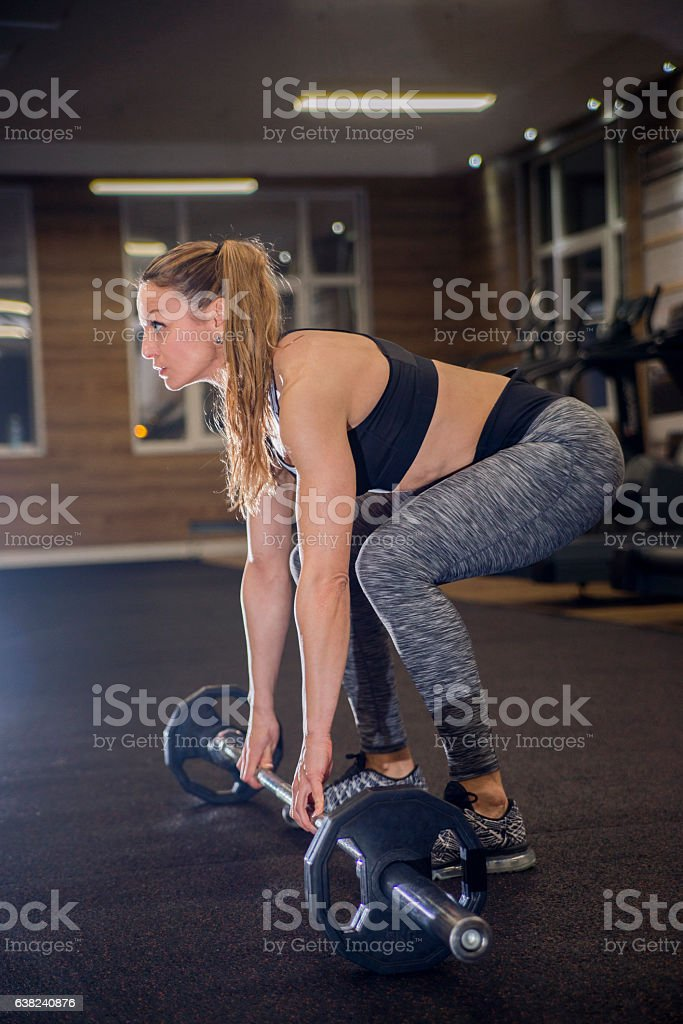 Beautiful woman in a private gym lifting weights stock photo
