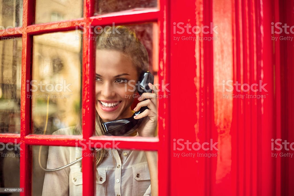 Beautiful woman in a red telephone booth stock photo