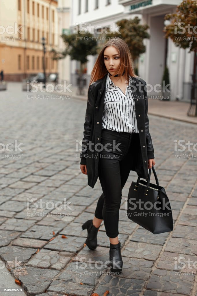Beautiful woman in a stylish black coat, fashionable autumn clothes with a bag near buildings in the city stock photo