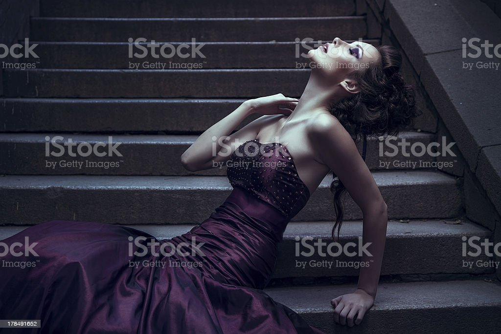 Beautiful woman in a violet dress for photography stock photo