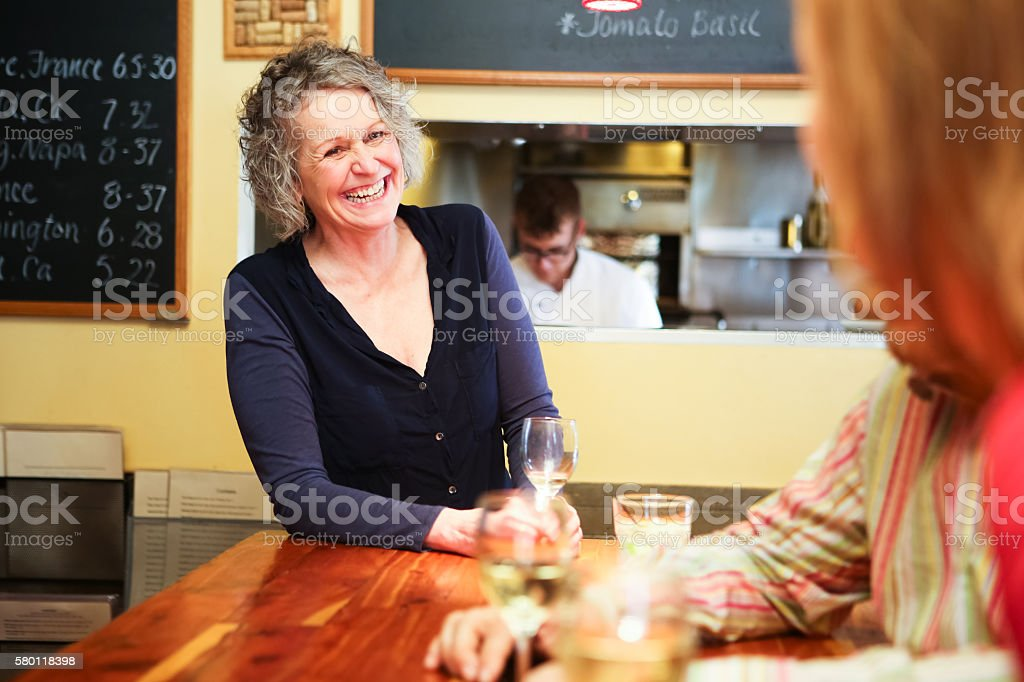 Beautiful Woman in Bar or Restaurant Laughing stock photo
