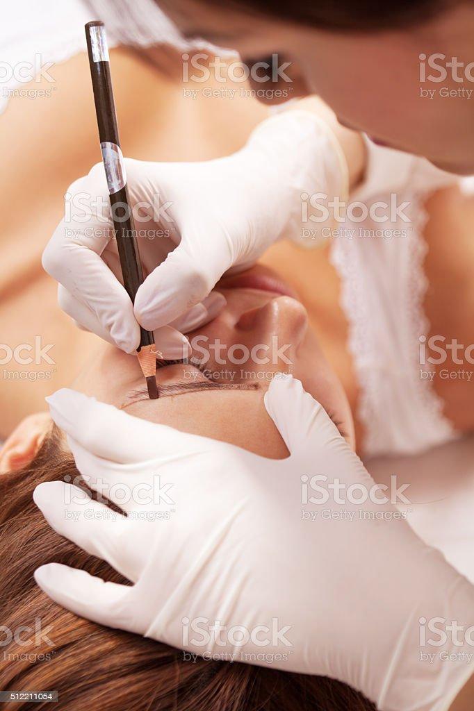 Beautiful woman in beauty salon on permanent eyebrow makeup trea stock photo