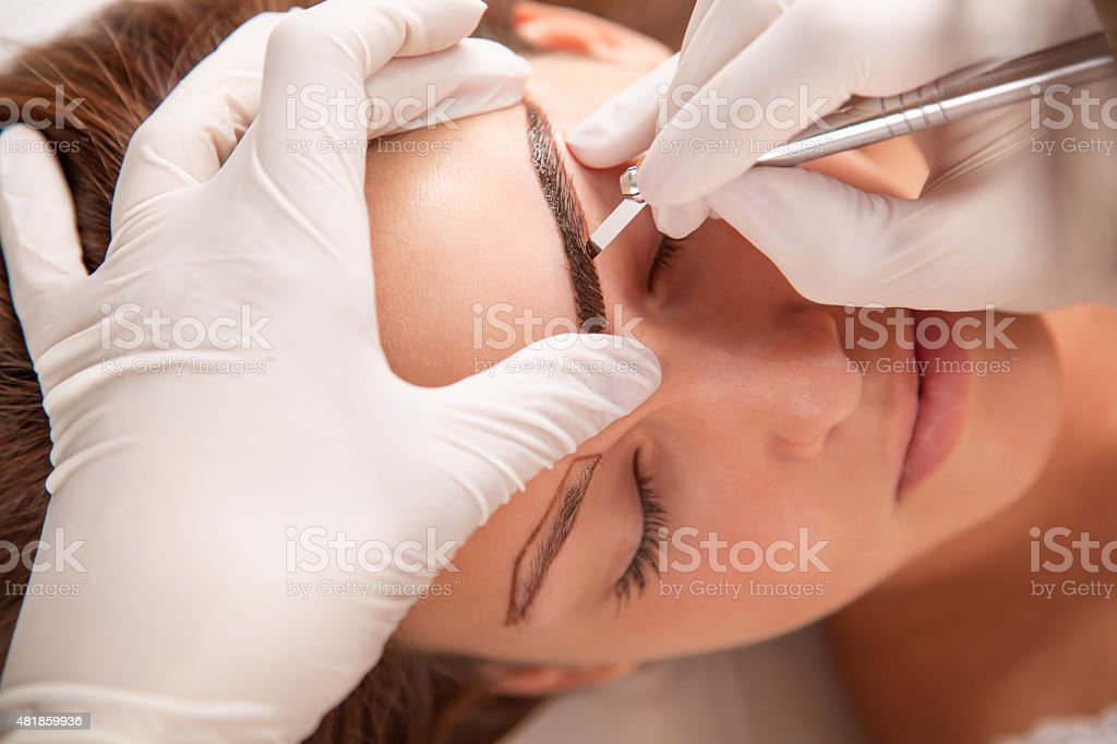 Beautiful woman in beauty slon on eyebrow makeup treatment stock photo