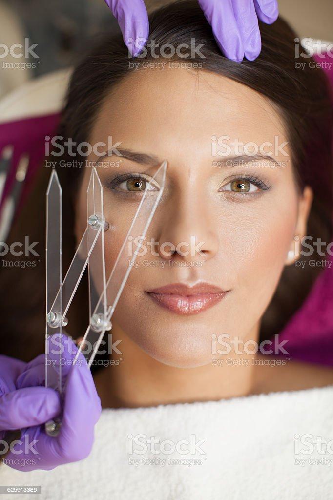 Beautiful woman in beauty slon on eyebrow makeup treatment stock photo