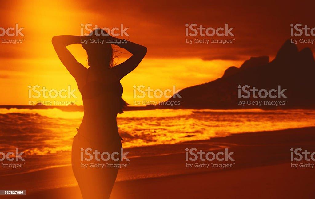 Beautiful woman in bikini at beach after swimming at sunset stock photo