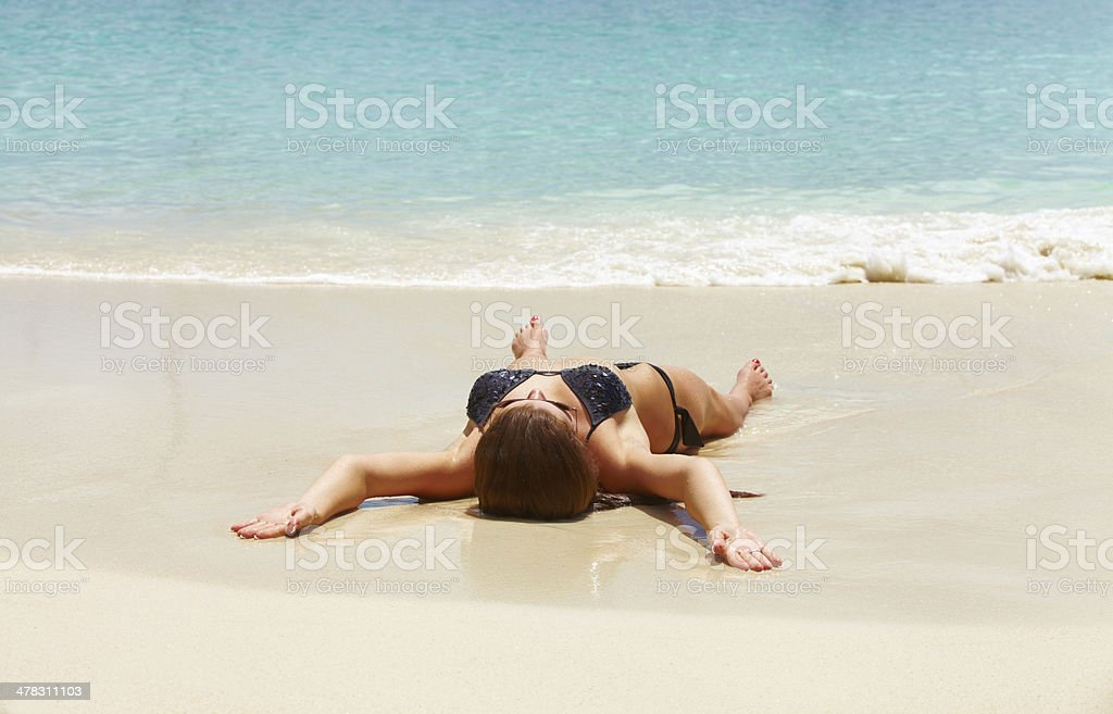 Beautiful woman in black bikini relaxing on the beach royalty-free stock photo