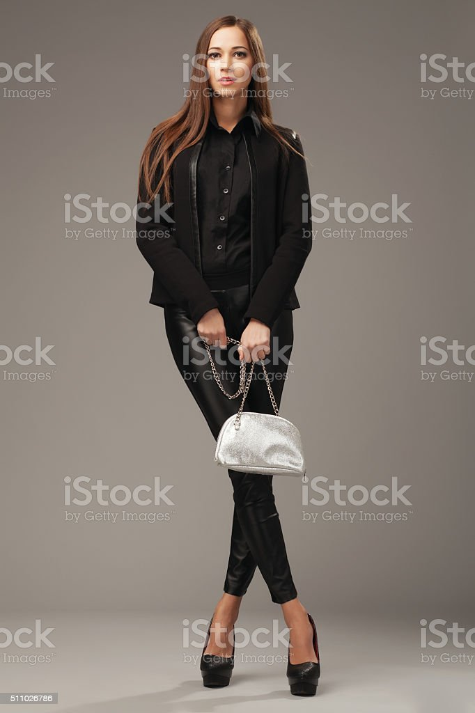Beautiful woman in black clothing with a silver fashion bag stock photo