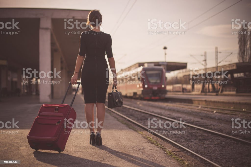 Beautiful woman in black drass carrying a suitcase traveling by train stock photo