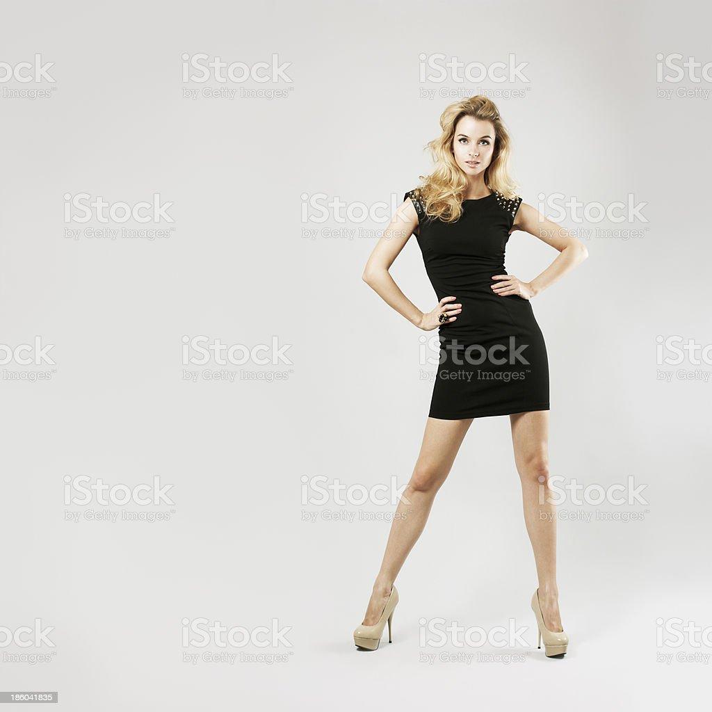 Beautiful woman in black dress posing on gray background stock photo
