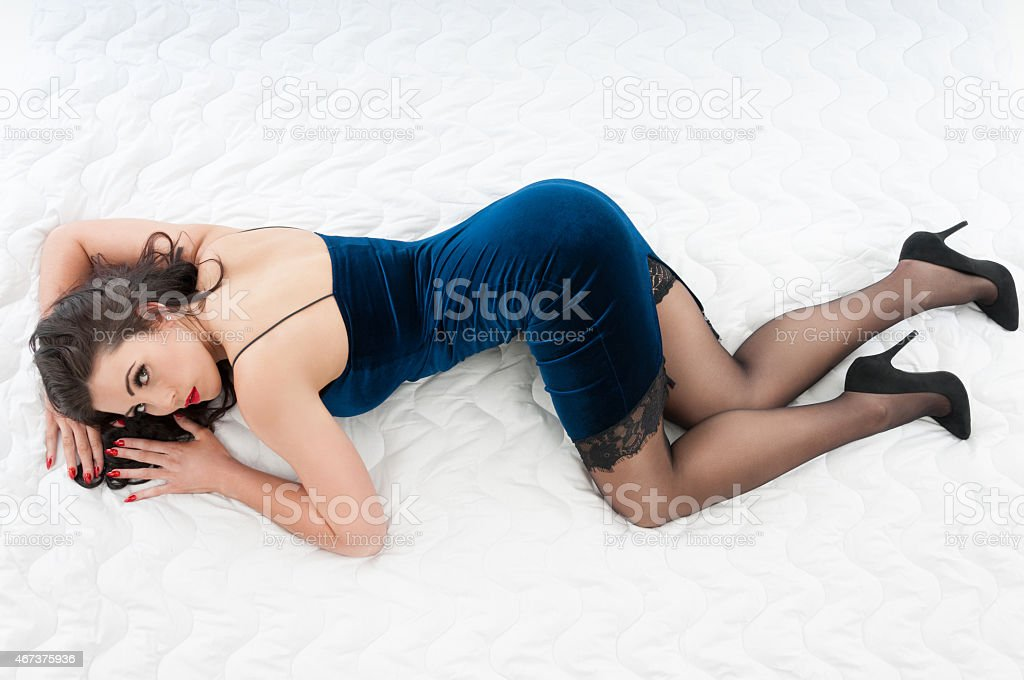 Beautiful woman in blue velvet bodycon dress stock photo