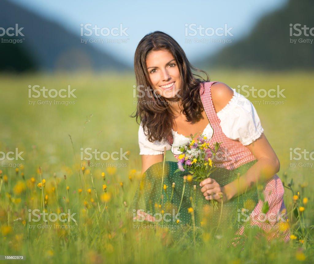 Beautiful woman in Dirndl Fashion picking Flowers (XXXL) royalty-free stock photo