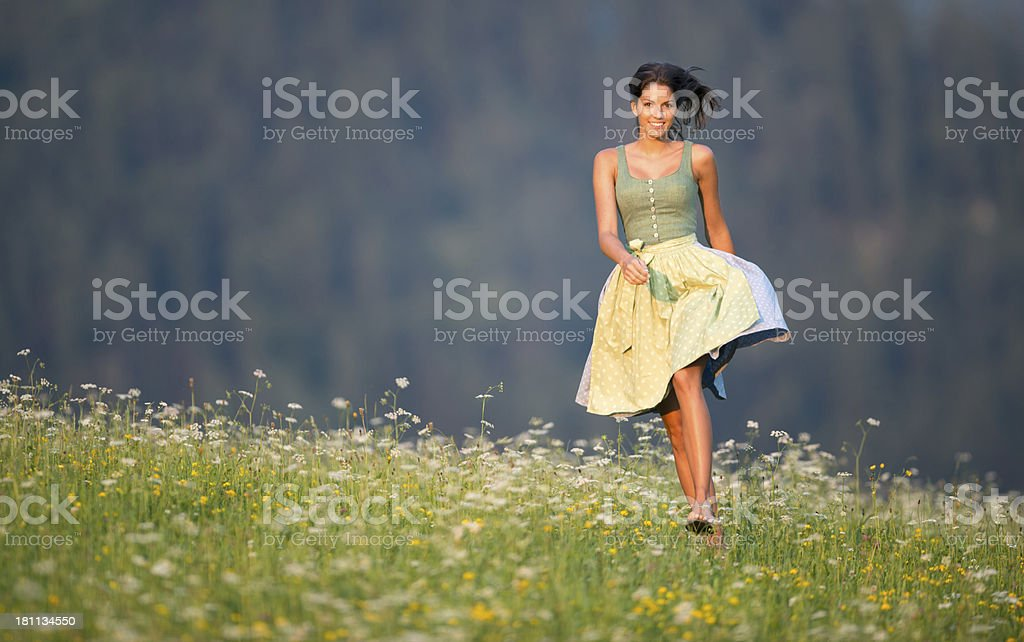 Beautiful Woman in Dirndl Fashion running through the Meadow royalty-free stock photo