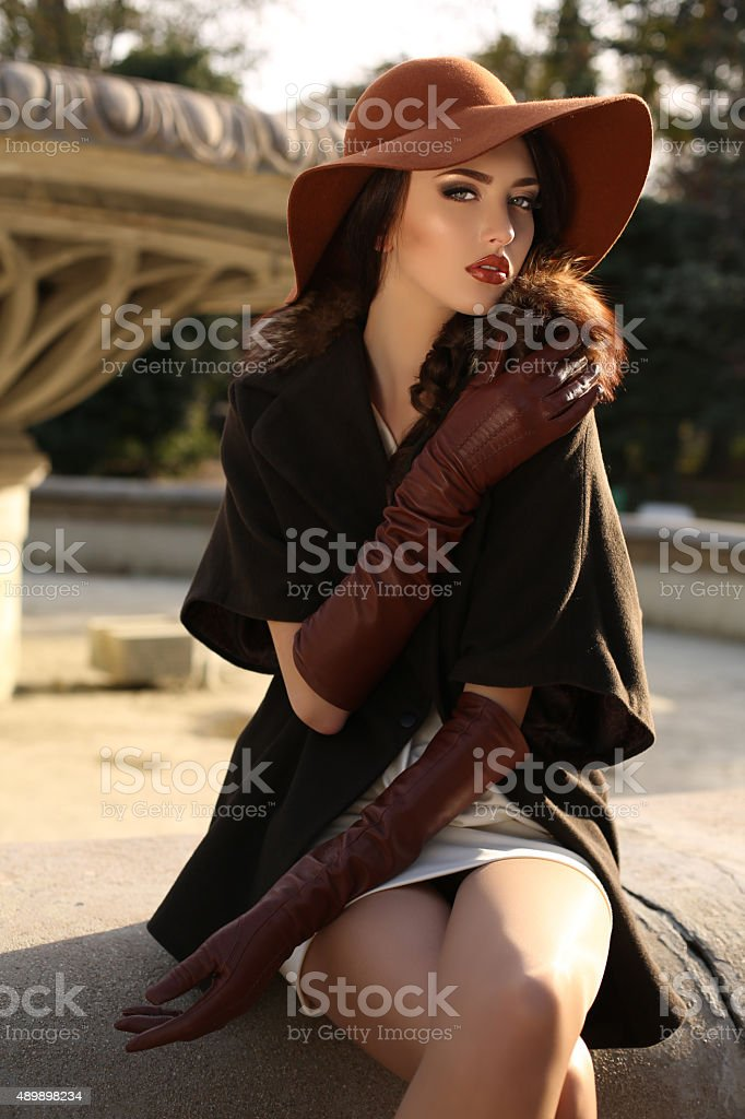 beautiful woman in elegant coat,gloves and felt hat stock photo