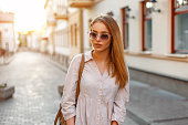 Beautiful woman in fashionable clothes and handbag with sunglasses