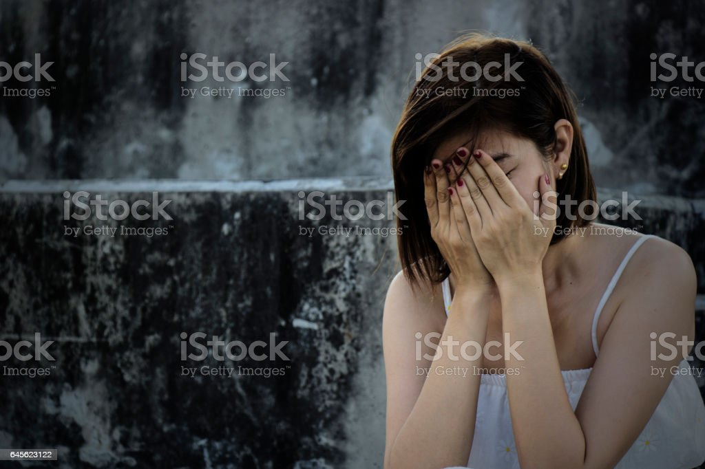 Beautiful woman in frustrated depression and crying. Conceptual of sadness and problems human in dark tone. stock photo