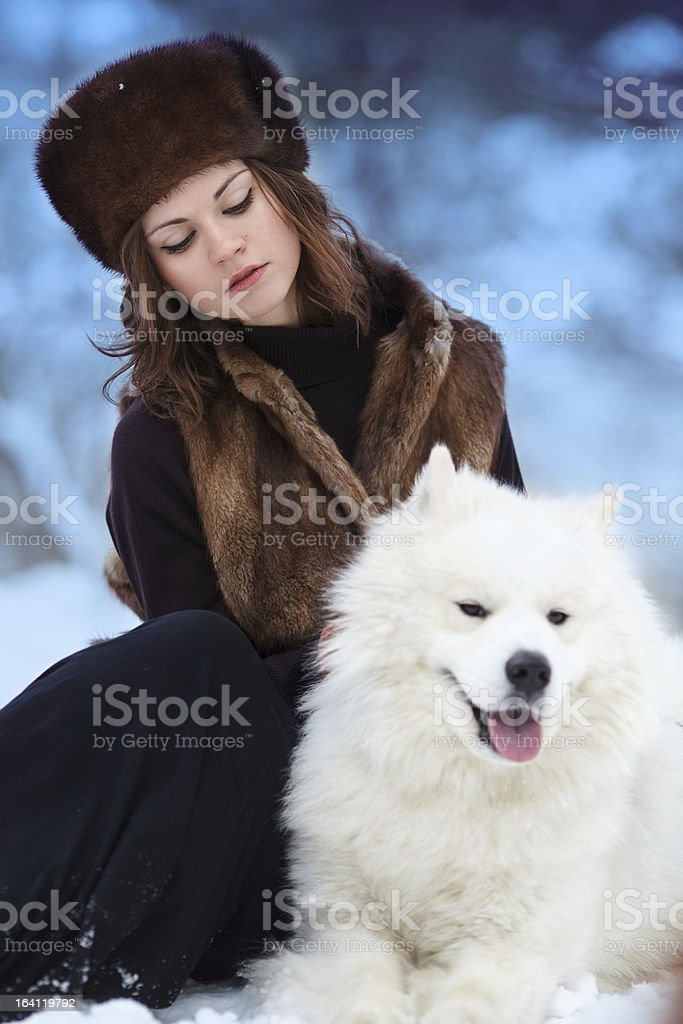 Beautiful woman in fur hat at winter forest with dog royalty-free stock photo