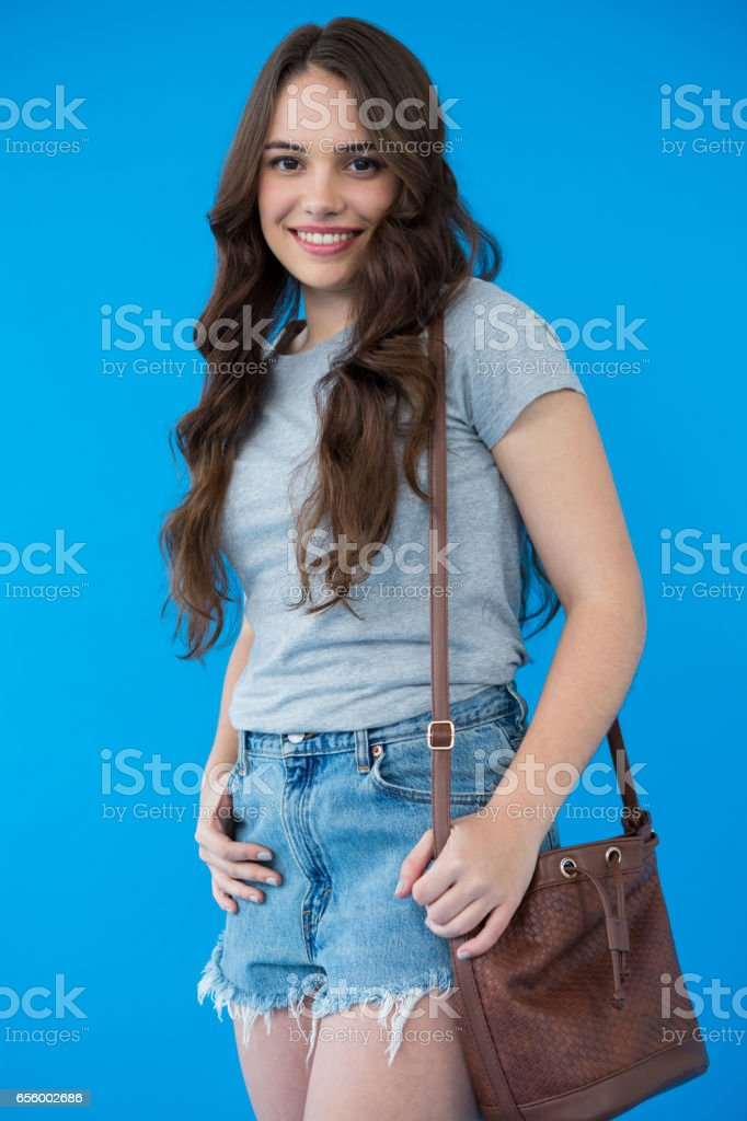 Beautiful woman in grey t-shirt with shoulder bag stock photo