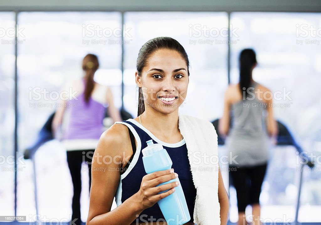 Beautiful woman in gym smiles as she takes a break stock photo