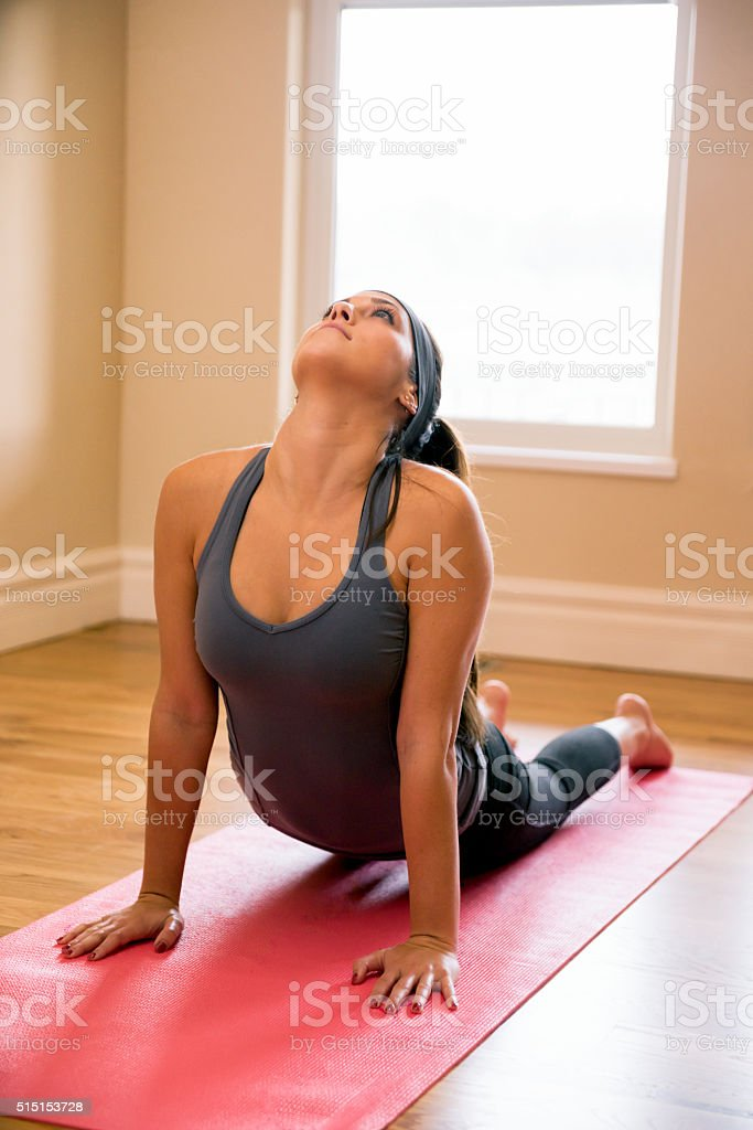 Beautiful Woman in Her 20s Doing Yoga Cobra Pose stock photo