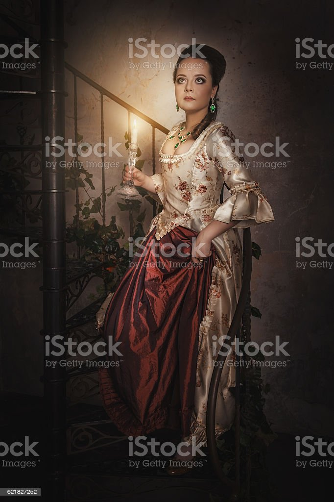 Beautiful woman in historic medieval dress with candle stock photo