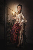 Beautiful woman in historic medieval dress with candle