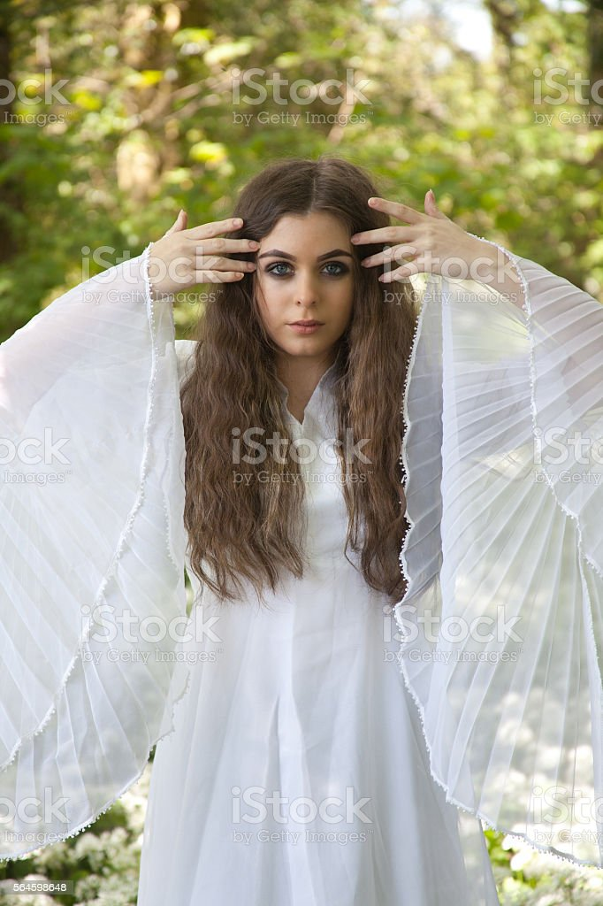 Beautiful woman in long white dress standing in a forest stock photo