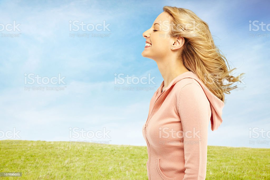 Beautiful woman in nature with the wind blowing her hair royalty-free stock photo